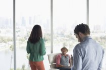 Casual business people in office overlooking city — Stockfoto