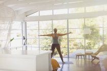Woman practicing yoga with arms outstretched in sunny modern bedroom — Stock Photo