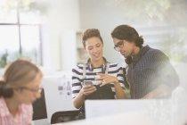 Gente creativa de negocios con auriculares que usan teléfonos inteligentes en la oficina - foto de stock