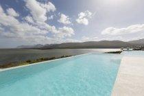 Soleggiata, tranquilla piscina a sfioro con vista sull'oceano — Foto stock