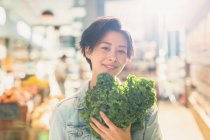 Portrait smiling young woman holding fresh kale in grocery store market — Stock Photo