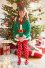Portrait smiling girl wearing elf costume in front of Christmas tree — Stock Photo