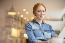 Happy young woman holding menu in cafe — Stockfoto