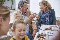 Happy senior couple toasting white wine glasses at patio lunch — Stock Photo