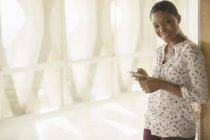 Portrait of smiling woman text messaging with cell phone in sunny corridor — Stockfoto