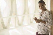 Portrait de femme souriante messagerie texte avec téléphone portable dans le couloir ensoleillé — Photo de stock