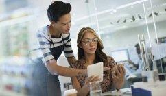 Mulheres de negócios criativas usando telefone inteligente e tablet digital no escritório — Fotografia de Stock