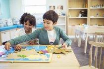 Étudiants faisant puzzle en classe — Photo de stock