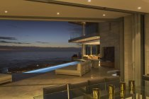 Illuminated home showcase patio with lap pool and twilight ocean view — Stock Photo