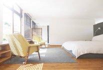 Кресла, ковёр и кровать в современной спальне — стоковое фото