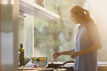 Woman cooking at stove in sunny kitchen — Stock Photo