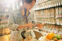 Junge Frau mit Kopfhörer benutzt Handy in Lebensmittelmarkt — Stockfoto