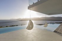 Sunny, tranquil modern luxury home showcase patio with hanging seats and infinity pool with ocean view — Stock Photo