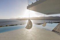 Soleggiato, tranquillo moderno patio vetrina di lusso con sedili pensili e piscina a sfioro con vista sull'oceano — Foto stock