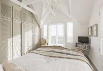Dormitorio blanco soleado tranquilo con techo abovedado - foto de stock