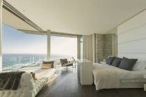 Luxury modern home showcase bedroom with sunny ocean view — Stock Photo