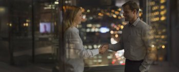 Businessman and businesswoman handshaking in office at night — Stock Photo