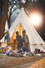 Students and teacher reading at teepee at campsite — Stock Photo