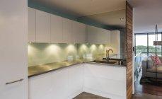 Illuminated modern, minimalist, luxury home showcase interior kitchen — Stock Photo