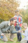 Father teaching sons to prepare fishing rods — Stock Photo
