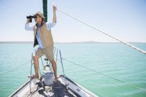 Older man looking out binoculars on edge of boat — Stock Photo