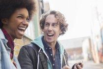 Пара, смеется вместе на городской улице — стоковое фото