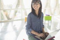 Heureuse femme d'affaires occasionnelle utilisant un ordinateur portable dans un bureau ensoleillé — Photo de stock