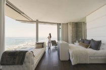 Woman looking at ocean view from modern luxury home showcase bedroom — Stock Photo