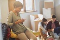 Jeune femme textos avec téléphone portable dans un nouvel appartement — Photo de stock