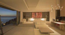 Iluminado, luxo casa vitrine interior quarto moderno com vista para o mar — Fotografia de Stock