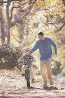 Père enseignant fils à faire du vélo sur la piste dans les bois — Photo de stock