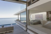 Modern, luxury home showcase living room and patio with ocean view — Stock Photo