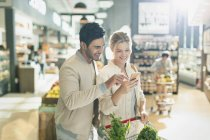 Young couple using cell phone, grocery shopping in grocery store market — Stock Photo