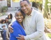 Закрыть портрет улыбающейся пожилой пары, обнимающейся на улице — стоковое фото