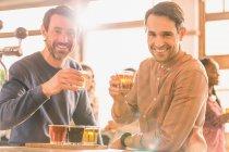 Portrait smiling men friends sampling beer at microbrewery bar — Stock Photo