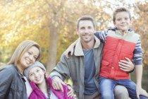 Портрет улыбающейся семьи перед деревом с осенними листьями — стоковое фото