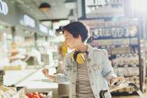 Giovane donna con le cuffie navigando, fare la spesa nel mercato — Foto stock