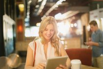 Smiling young woman using digital tablet and drinking coffee in cafe — Stock Photo