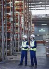 Workers with clipboards looking away in distribution warehouse — Stock Photo