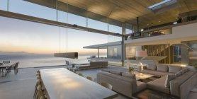 Современные, роскошные дома витрина гостиная и столовая открыт для видом на океан в сумерках — стоковое фото
