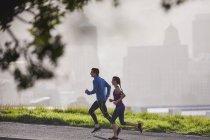 Couple coureur courant sur la rue urbaine ensoleillée — Photo de stock