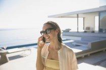 Улыбающаяся женщина разговаривает по смартфону на солнечном современном роскошном внутреннем дворике — стоковое фото
