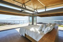 Modern luxury bed open to patio with sunny ocean view — Stockfoto