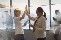 Businesswomen with digital tablets high-fiving in conference room — Stock Photo