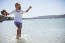 Giovane ragazza schizzi in acqua sulla spiaggia — Foto stock