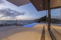 Patio with lap swimming pool and ocean view at dusk — Stock Photo