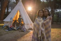 Girls wrapped in blanket at campsite — Stock Photo