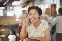Улыбающаяся молодая женщина разговаривает по телефону в кафе — стоковое фото