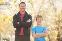 Портрет уверенный отец и сын с скрещенными на улице руками — стоковое фото
