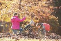 Ragazzi e ragazze che giocano in autunno foglie — Foto stock